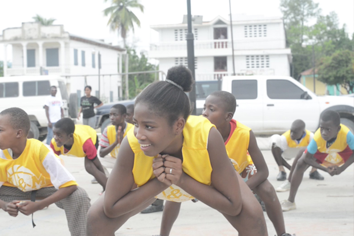 A young girl having fun during the stretching portion of our workshop in Hinche.